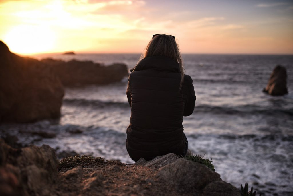 Woman sitting by the sea. Use kratom for opiate withdrawal