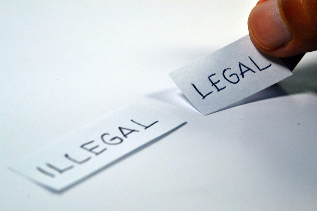 Two small pieces of paper with legal and illegal written on the, placed on a white surface.
