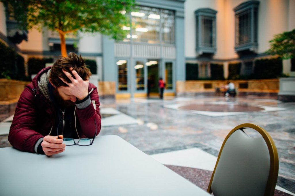 Man holding his head and eyeglasses sitting beside a table feeling anxious