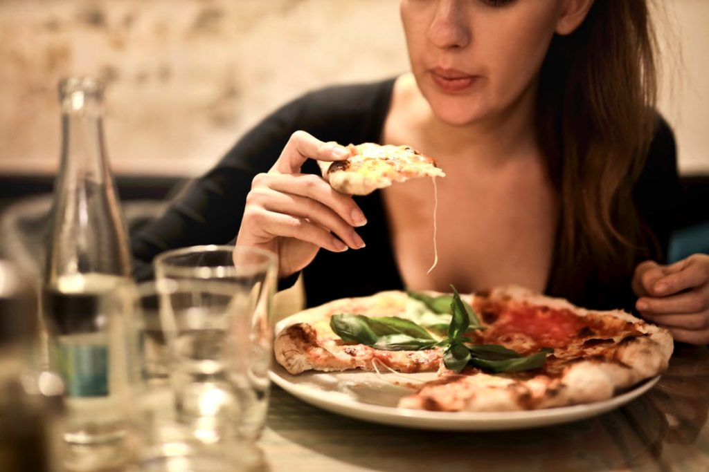 Woman eating Italian pizza from a white ceramic plate.