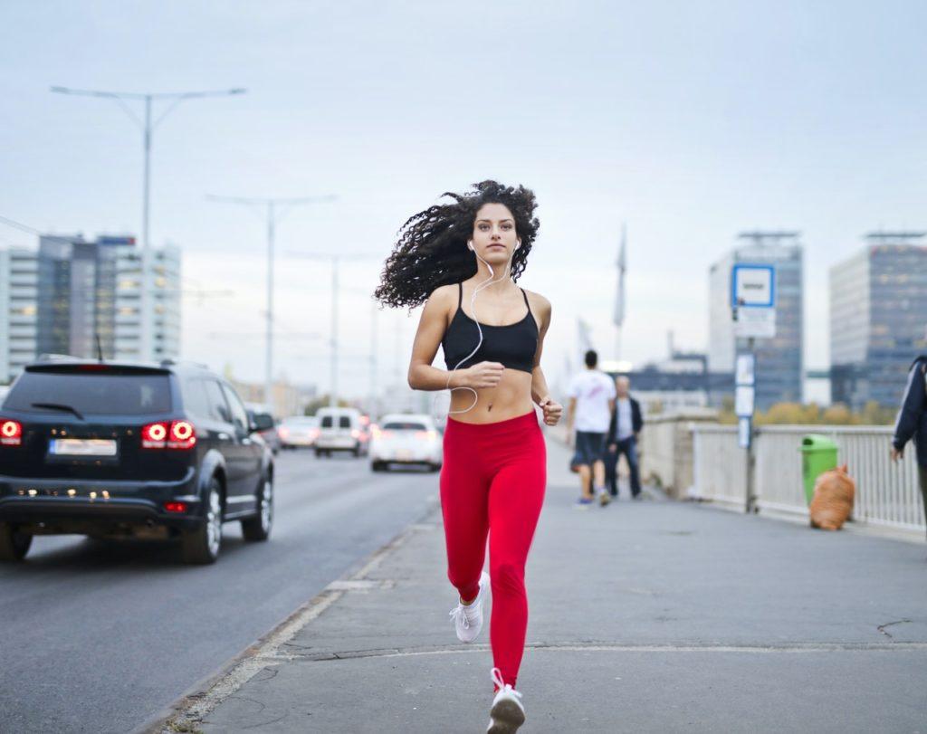 Woman jogging on a sidewalk.