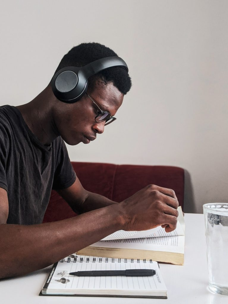 A man wearing headphones probably listening to music while reading a book.