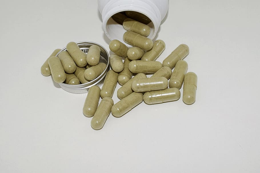 Herbal supplement capsules on a white surface.