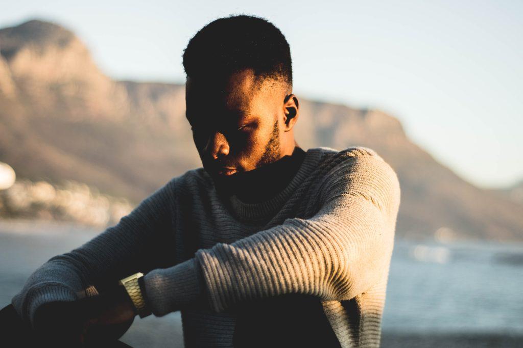 A man looking depressed sitting outdoors. Can kratom help?