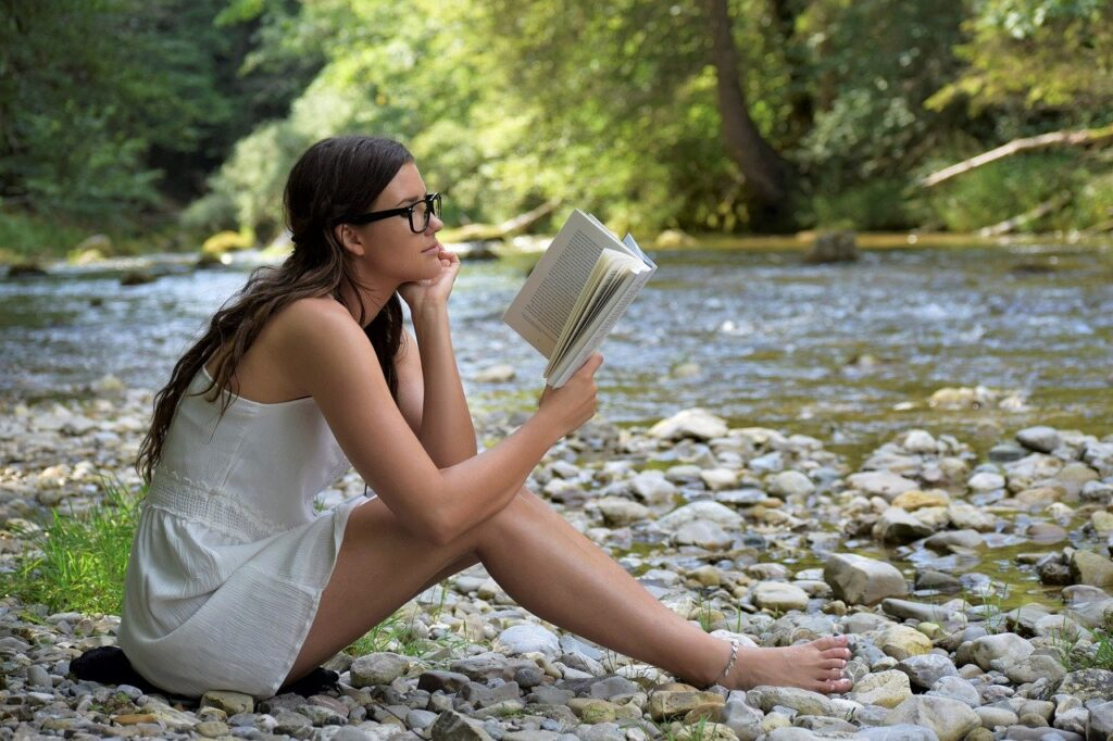 A woman looking intelligent while reading outdoors. Reading can improve cognitive function, it is also reported that the white hulu kratom can help with that too.